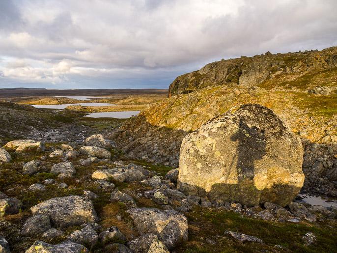 Vaeltaja hetken kivessä, leiripaikka edessä veden äärellä. Gottetjavrrit, Norja