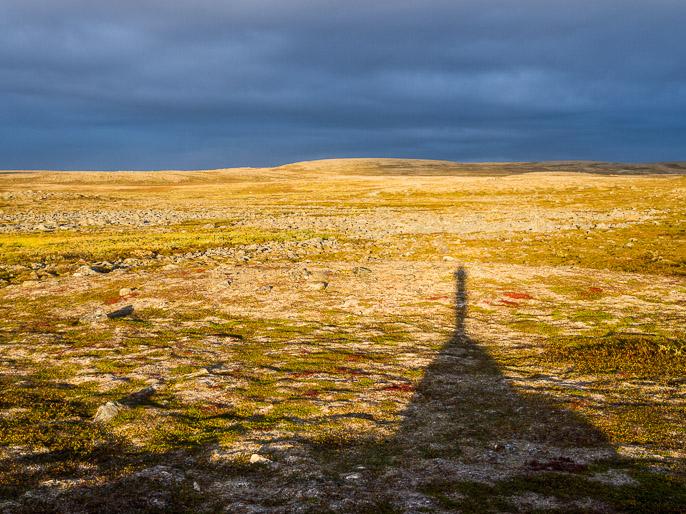 Kiva ilta-aurinko seistä ympäristön suurimman kiven päällä, mutta epäilyttävän tummat pilvet ovat kerääntymässä. Gottetjavrrit, Norja