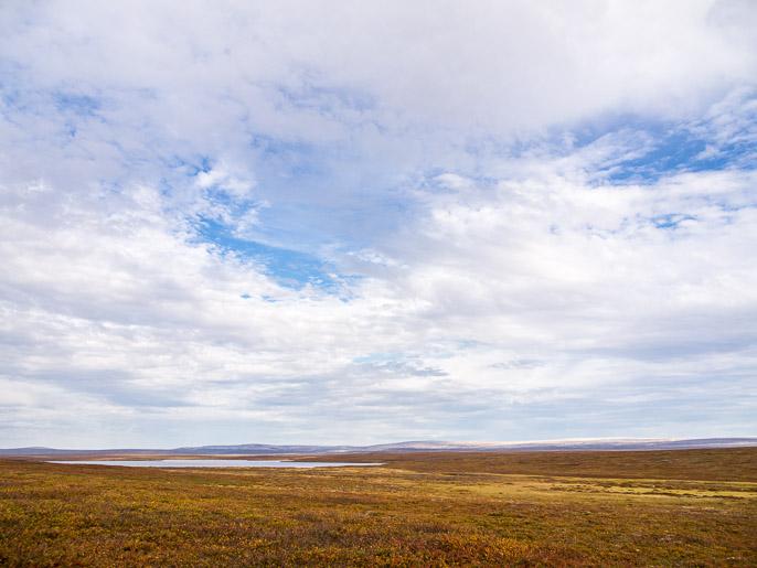 Järven alapuolelta oikealla kaartaen, kaukaisuudessa valkoista heijastavat kivikasat. Suovvejavri, Norja